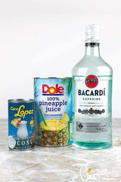 pina colada ingredients - one can of coco lopez, one large can of pineapple juice and a bottle of bacardi light rum on table.