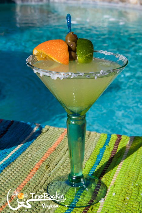 The Mexican Martini Drink with garnish of olives, orange and lime by the pool.