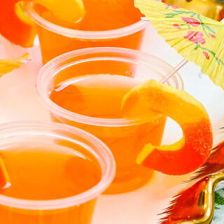 Peach Vodka Jello Shots with Peach Rings garnish and Drink Umbrella up close.