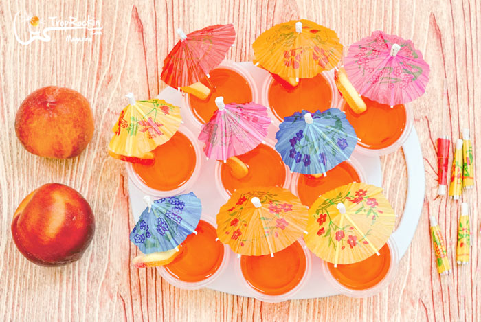 Peach vodka jello shots with drink umbrellas on serving tray